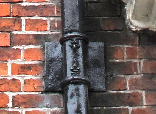 The repeating motif of a fleur de lys on the rainwater bracket